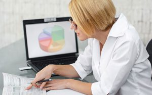Woman with glasses references book with colorful pie chart on her laptop behind her