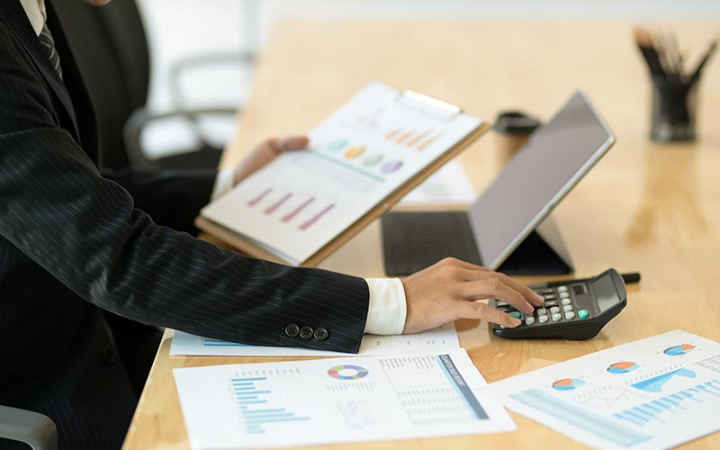 Business person in pin-stripe suit uses calculator while looking at graphs & charts