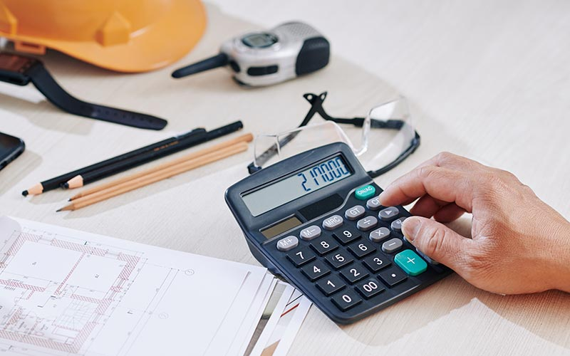 hand using calculator on desk with construction items