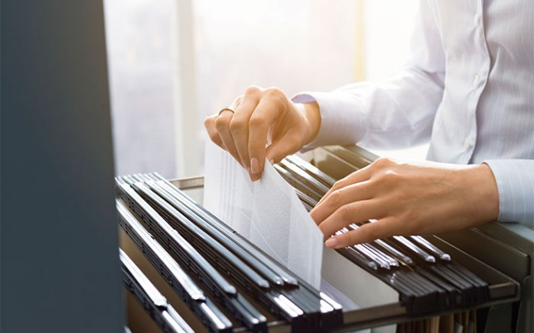 Woman's hands as she checks file cabinet