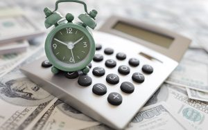 Green alarm clock on top of a calculator and money