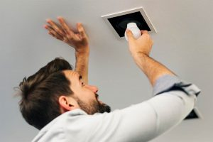 Man installing a lightbulb in a ceiling light