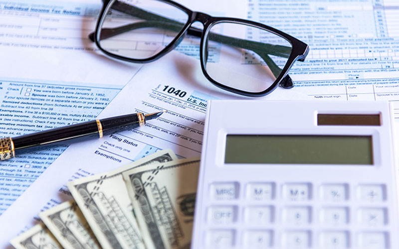 Glasses, quill, white calculator and money on top of tax returns