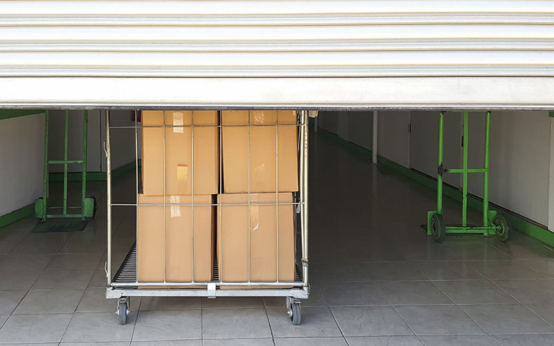 Boxes in a cart behind a warehouse door