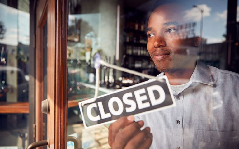 African American man turning a closed sign on the front of his business