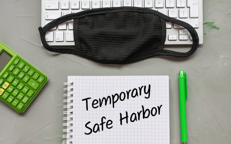 "Keyboard with a mask on top of it with a notebook that says ""Temporary Safe Harbor"""