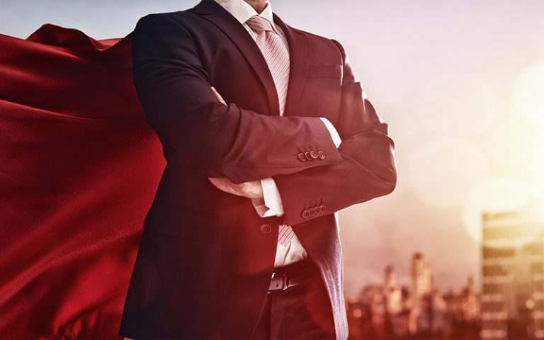 Businessman confidently posing with a cape
