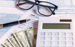 Calculator and money on top of tax forms
