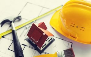 Construction tools and a house miniature on top of building plans