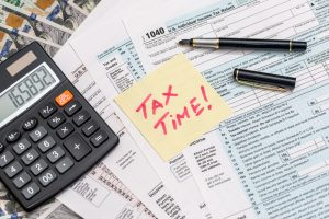 Tabletop with tax forms, calculator, and a sticky note that says Tax Time!